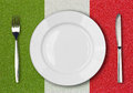 White plate, fork and knife on italian flag Royalty Free Stock Images