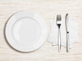 White plate knife fork and napkin top view on wooden table Stock Images