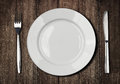 White plate, knife and fork on old wooden table Royalty Free Stock Photo