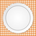 White plate on orange tablecloth empty over checkered background Royalty Free Stock Image