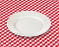 White plate over red picnic tablecloth checked Stock Image