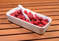 White plate with raspberry on wooden background Royalty Free Stock Photography