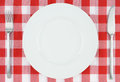 White plate on red and white checkered cloth Stock Photos