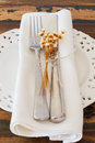 White plate serviette fork knife dried flowers Royalty Free Stock Photo