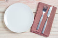 White plate and silverware on table Royalty Free Stock Photo