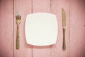 White plate, vintage fork and knife  on rustic pink wooden table. Royalty Free Stock Photo