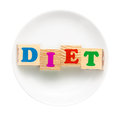White plate with word diet composed of wooden cubes isolated on a background dieting concept Royalty Free Stock Photography