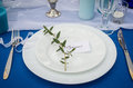 White plates on the banquet table with guest's name Sergei and a branch of eucalyptus.