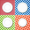 White plates on checkered tablecloth Stock Photography