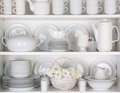White plates in cupboard closeup of and dinnerware a a basket of roses is centered on the bottom shelf items include Royalty Free Stock Images