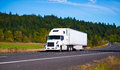 White popular luxe semi truck trailer on scenic highway Royalty Free Stock Photo