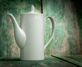White porcelain coffee pot on wooden background Royalty Free Stock Photo