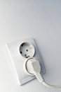 White power electrical outlet double on the wall with one cable plugged in Royalty Free Stock Image