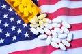 White pharmaceutical pills spilling from prescription bottle over American flag Royalty Free Stock Photo