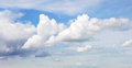 White puffy clouds in blue sky Stock Photography