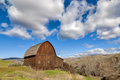 White puffy clouds and old brown barn Royalty Free Stock Photos