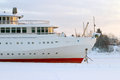 White and red prow of ship with an anchor in frozen river in winter day Stock Photo