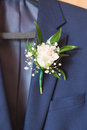 White rose boutonniere pinned to a grooms jacket. Royalty Free Stock Photo