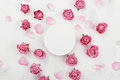 White round blank, pink rose flowers and petals for spa or wedding mockup on light background top view. Beautiful floral pattern. Royalty Free Stock Photo