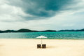 White sand beach with two sunbeds umbrella without people luxury resort and stormy sky mountains background Royalty Free Stock Image