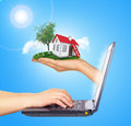 White shack in hand with red roof and chimney of brown door screen laptop hands typing on keyboard background sun shines brightly Stock Photo