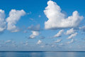 White ships freakish clouds in the sky and a strip of the blue sea Royalty Free Stock Photos