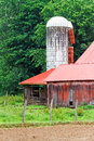 White silo and red barn an old weathered stands by an old with a metal roof in the agrarian countryside of south central ohio Stock Photos