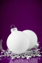 White and silver christmas ornaments on dark purple background with space for text. Royalty Free Stock Photo