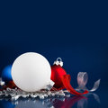 White, silver and red christmas ornaments on dark blue background with space for text. Royalty Free Stock Photo