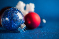 White, silver and red christmas ornaments on dark blue glitter background. Royalty Free Stock Photo