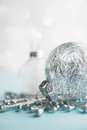 White and silver xmas ornaments on glitter bokeh background. Merry christmas card. Royalty Free Stock Photo