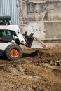 White skid steer loader at a construction site working with a soil. Industrial machinery. Industry. Royalty Free Stock Photo