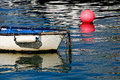 White skiff with pink buoy small a float reflected in harbour waters Royalty Free Stock Images
