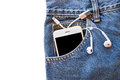 White smartphone in your pocket blue jeans with earphone and USB cable for transfer data or information Royalty Free Stock Photo