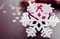White snowflake on background of magenta and gold xmas baubles. Royalty Free Stock Photo
