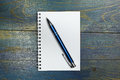 White spiral notebook with pen on old blue wooden table Stock Photo