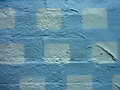 White squares painted on a blue painted wall with peeling paint Stock Photo