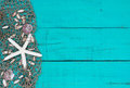 White starfish and shells in fish netting on teal blue wood beach sign Royalty Free Stock Photo