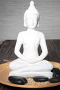 White statue meditating buddha sitting earthenware bowl smooth black basalt massage stones spa tranquillity relaxation Royalty Free Stock Photo