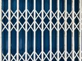 White steel folding door with a blue metal sheet background