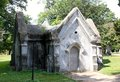White stone burial crypt a heavily weathered mausoleum situated in a cemetery Stock Images