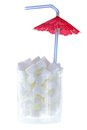 White sugar cubes with cocktail umbrella a glass of and drinking straw Royalty Free Stock Images