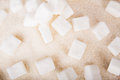 White sugar cubes and crystal sugar on a wooden background Stock Photo