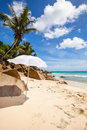 White sunshade at la digue beach the tropical of seychelles with palm granite rocks and blue sky Stock Photo