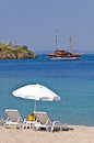 White sunshade with two chairs on a sandy beach with ship anchored by the old roman fortress in a background, Sithonia Royalty Free Stock Photo