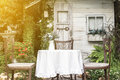 White table and chairs in beautiful garden. Royalty Free Stock Photo