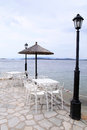 White tables and chairs on sea pier greece umbrella Stock Images