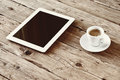 White tablet computer with cup coffe on a wooden table top view copy space free space for text office desk mock up vintage toning Royalty Free Stock Photos