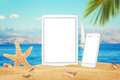 White tablet and smart phone with isolated white screen for mockup. Summer on beach, sea, sand, blue sky, palm, starfish and shell Royalty Free Stock Photo