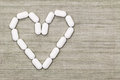 White tablets in a heart shaped symbol with copyspace top view of Stock Photo
